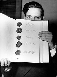 Ein Mitarbeiter zeigt eine Seite mit einigen der Unterschriften und Siegel des östereichischen Staatsvertrages nach der Unterzeichnung am 15. Mai, 1955 in Wien.