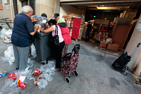 Älterer Mann durchwühlt Müllcontainer
