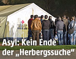 Asylwerber vor einem Zelt des Roten Kreuzes