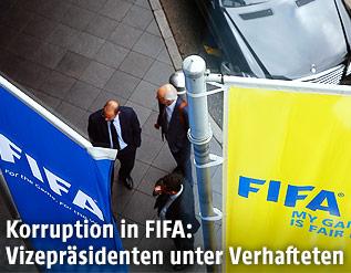 Männer stehen unter zwei FIFA-Fahnen