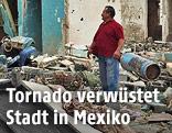 Mann steht vor den Trümmern zerstörter Häuser