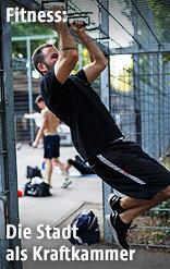 Sportler zieht sich an Eisenstange hoch