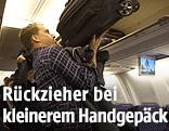 Mann verstaut sein Handgepäck im Flugzeug