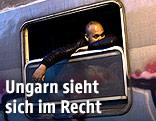 Migrant wartet in einem stillstehenden Zug nahe dre ungarischen Grenze und sieht aus dem Fenster