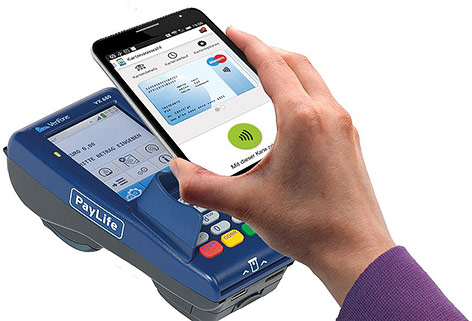 Person hält Smartphone über Bankomatgerät