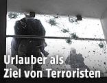 Umriss einer bewaffneten Person vor einer zerschossenen Fensterscheibe