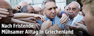 Griechischer Bankmitarbeiter, von Pensionisten umringt