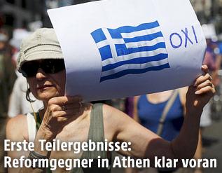 """Eine griechische Frau hält ein Plakat mit der Aufschrift """"Oxi"""" (""""Nein"""") hoch"""
