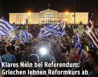 Jubelnde Menschen mit Flaggen vor dem griechischen Parlament