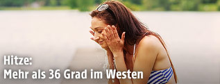 Junge Frau kühlt sich am See ab