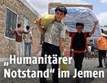 Syrische Kinder tragen Hilfsgüter