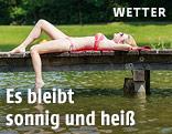 Frau liegt auf einem Badesteg