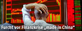 Ein chinesischer Börsenhändler vor einem Monitor mit Börsenkursen