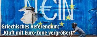 """Radfahrer vor einem """"Nein"""" auf einer Euro-Flagge, dass auf eine Wand gesprayt wurde"""