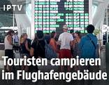 Touristen vor einer Anzeigetafel auf dem Flughafen von Bali