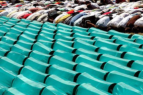 Menschen beten vor Särgen der Opfer von Srebrenicamassaker