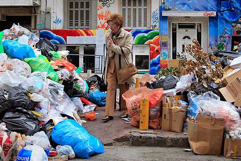 Eine Frau geht an Müllbergen vorbei