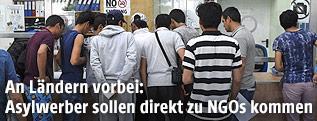 Asylwerber stehen an einem Infopoint