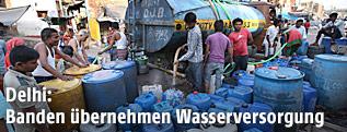 Menschen füllen Wasser von einem Tankwagen in Kanister