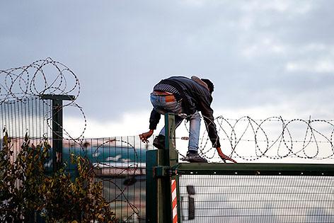 Flüchtling klettert über einen Zaun