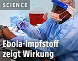 Eine Krankenschwester mit Ganzkörperschutz verabreicht eine experimentelle Ebola-Imfpung