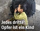 Kind liegt auf einem Rucksack