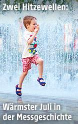 Ein Bub springt durch das Wasser eines Springbrunnens