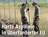 Soldaten bauen einen Grenzzaun auf