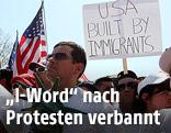 """Mann hält ein Schild mit der Aufschrift """"USA build by immigrants"""" in die Höhe"""