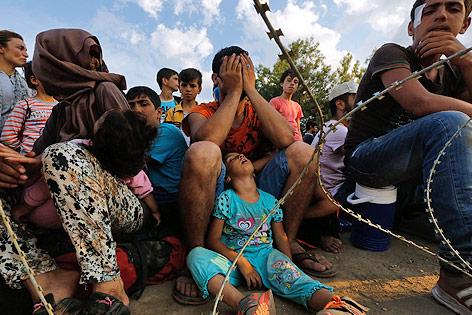 Syrische Flüchtlinge hinter einem Stacheldrahtzaun