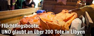 Leichensäcke werden auf einen Lastwagen verladen