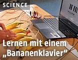 An einem Laptop mit Kabeln angeschlossene Bananen