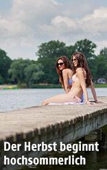Junge Frauen sitzen auf einem Steg bei einem See