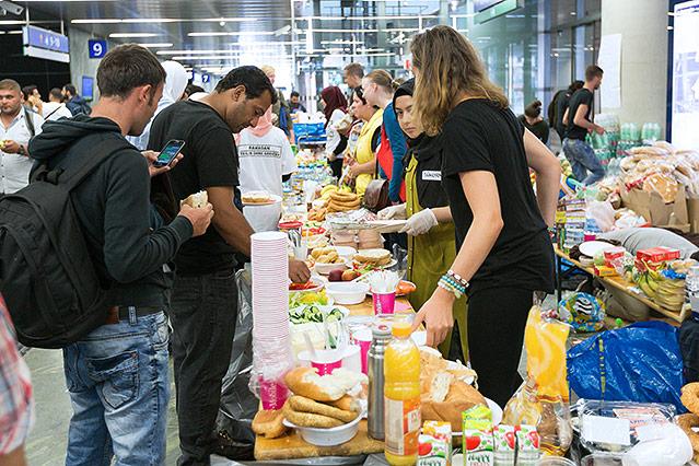 Freiwillige geben Essen am Westbahnhof aus