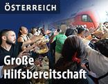 Menschen am Westbahnhof verteilen Essen und Getränke an Flüchtlinge