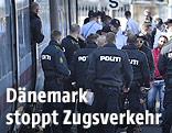 Dänische Polizisten mit Migranten neben einem Zug