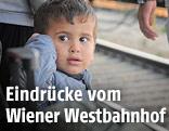 Kind sitzt auf einem Bahnsteig