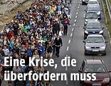 Marschierende Menschenmassen neben fahrenden Autos