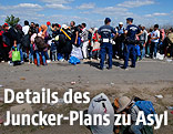 Migranten stehten neben ungarischen Polizisten in einer Schlange