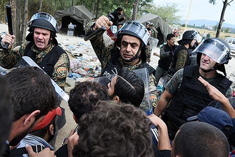 Polizisten und Flüchtlinge an der griechisch-mazedonischen Grenze