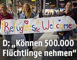 """Menschen halten ein Plakat mit der Aufschrift """"Refugees Welcome"""""""