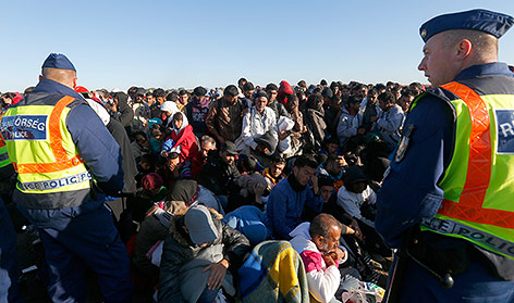 Menschen sitzen auf dem Boden und warten auf Transportbusse