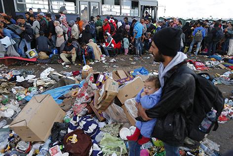 Flüchtlinge warten bei einem Sammelpunkt in Röszke auf den Bus