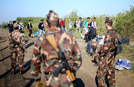 Soldaten beobachten Flüchtlinge
