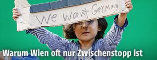 """Mädchen mit """"We want Germany"""" -Schild"""