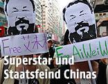 Zwei Frauen tragen ein Bild des chinesischen Künstlers Ai Weiwei vor ihrem Gesicht