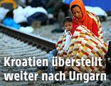 Mutter mit Kind sitzt in Decken eingehüllt auf den Bahngleisen auf dem Bahnhof Tovarnik, Kroatien
