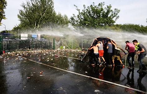 Flüchtlinge suchen hinter einem Zelt  Schutz vor der ungarischen Polizei und deren Einsatz von Wasserwerfern