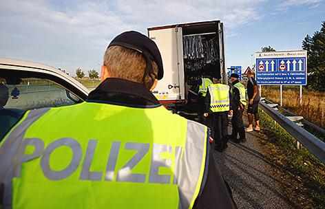 Polizisten kontrollieren einen Lkw an der Grenze in Nickelsdorf