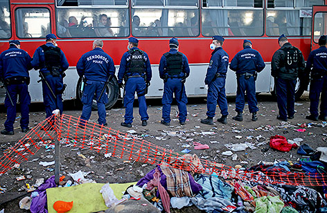 Ungarische Polizisten stehen vor einem Bus mit Flüchtlingen